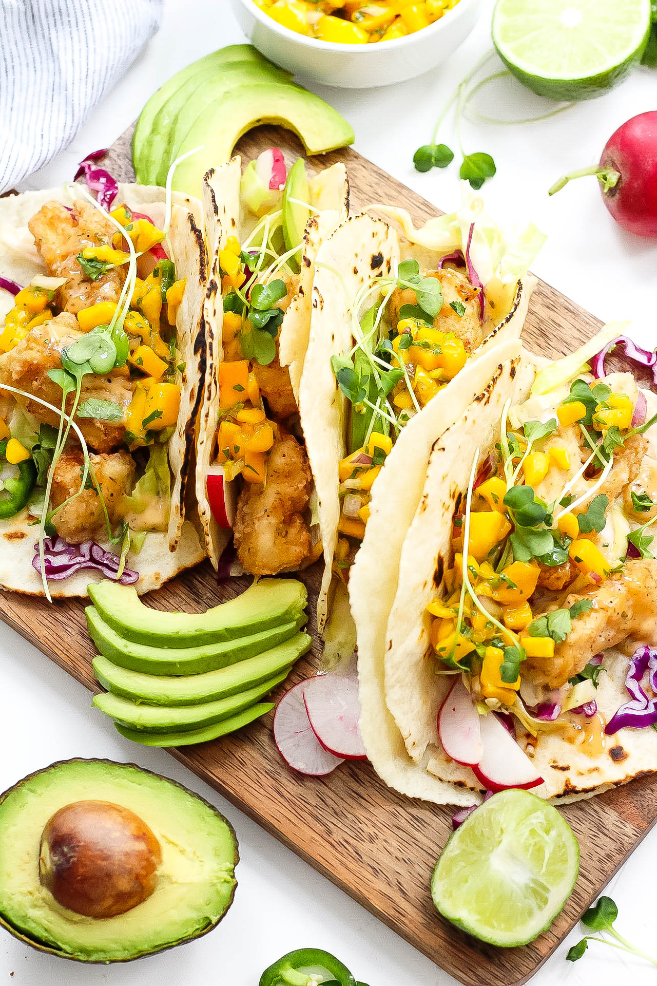 These grain free tacos is a fun and quick breaded fish recipe with easy mango salsa! Paleo fish tacos are totally gluten-free, family friendly, and even Whole30 if you skip the grain free tortilla and go for a lettuce wrap fish taco! Either way, these paleo fish tacos will be a summer favorite! #paleofishtacos #grainfreetacos #paleofish