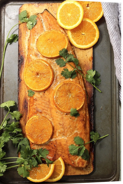 This Whole30 and Paleo orange glazed cedar plank salmon is every bit as delicious and easy as it looks! It's one of my favorite simple ways to cook salmon. The Paleo orange glaze takes a minute to put together and the cedar ramps up the taste of the salmon even more! #whole30salmon #whole30grilling #cedarplanksalmon