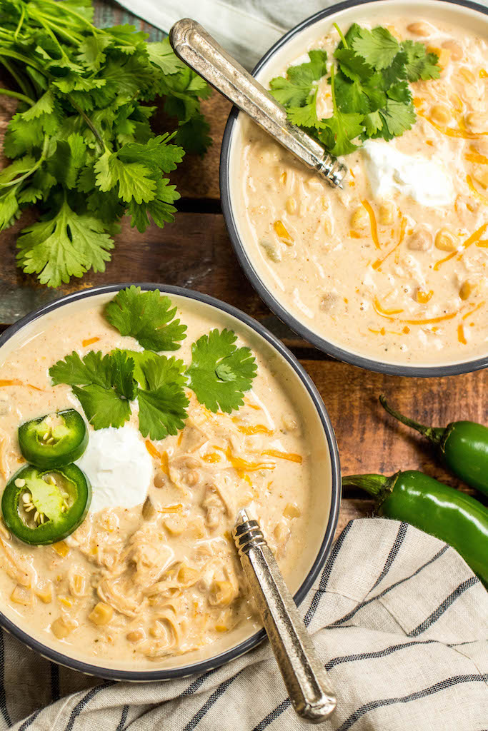 This slow cooker white chicken chili is a family recipe I grew up with, and it's every bit as hearty and delicious as it is easy to make. It's made with a few simple ingredients like white corn, shredded chicken, cream cheese, northern beans and the perfect spice combination. With only a couple of minutes of prep work, this hands off dinner is a great recipe for a chilly fall or winter night. #slowcookerchili #whitechickenchili #slowcookerwhitechickenchili