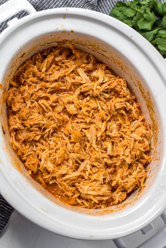 This slow cooker buffalo chicken could not get any easier. It's a Paleo, Whole30 and Keto meal that you can just dump into the slow cooker and come back later to find dinner ready. It's also a great meal prep recipe that can be used for buffalo chicken salads, wraps, tacos and much more. #whole30 #whole30buffalochicken #buffalochicken #slowcookerbuffalochicken #ketoslowcooker #paleo