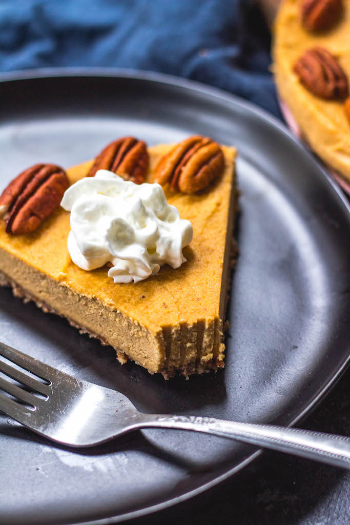 This paleo pumpkin cheesecake is the perfect dairy free and gluten free fall dessert. It's a no bake treat that everyone will love and that only takes a few minutes to prepare in a blender, or food processor. With a delicious pecan crust and creamy pumpkin filling, whether you serve this at a holiday or a cool fall weekend, it's sure to be a hit! It can also easily be made vegan! #paleodessert #paleocheesecake #dairyfreecheesecake #pumpkincheesecake #paleopumpkin