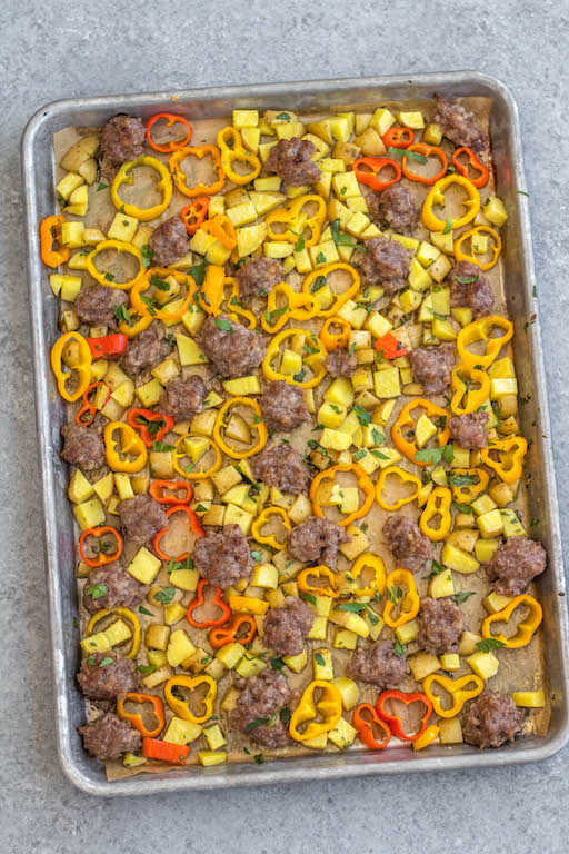 This easy sheet pan sausage breakfast recipe is a healthy meal prep recipe that's only 5 ingredients! The breakfast sausage is paired with seasoned potatoes and peppers all on one pan, put into the oven and ready to go with very little hands-on time. It's also great for a weeknight dinner for a simple vegetable and protein meal. This is a quick Whole30, paleo, gluten-free and egg-free breakfast recipe the whole family will enjoy! #whole30breakfast #whole30sheetpan #sheetpanbreakfast #glutenfree #eggfree #paleobreakfast