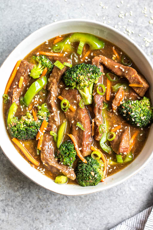 This easy slow cooker Mongolian beef is quick to throw into the crock pot, and is Whole30, Paleo, low carb and gluten-free. It only needs a handful of simple ingredients to make the sauce, along with flank steak, carrots, bell pepper and broccoli for the vegetables. This family friendly meal is perfect for dinner or for a healthy meal prep recipe! #whole30recipes #whole30beef #mongolianbeef #slowcooker #crockpot